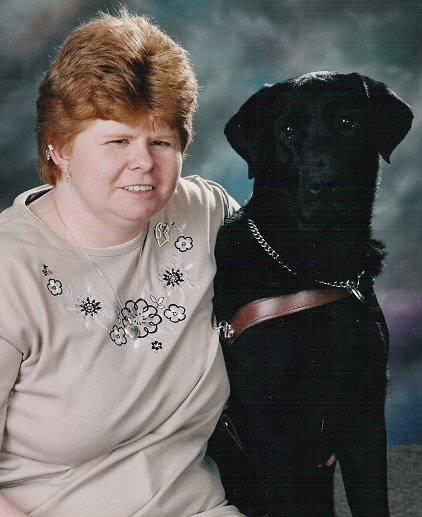 Karen Ann & Gwendy  I met my girl Gwenyth at GEB March 4, 1999.  She was a female version of Merlin... a gorgeous black Labbie girl with personality plus!  Gwendy was my perfect girl.  Her guide work was superb and she loved leaping into that harness.  I thought Gwendy would be the dog that would be with me forever... but sadly she developed a rare neuro-muscular disease at the young age of 6 yrs.  She passed away three months after she was diagnosed.  I held her and bid a tearful so-long on Aug. 13, 2003.  I miss that girl more then words can tell.